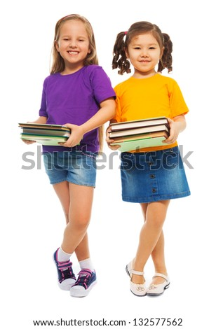 Two happy little girls Asian and Caucasian with books standing isolated on white, full height portrait
