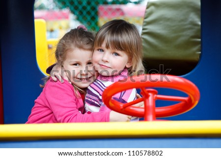 Two happy little girls embracing on playground at summer day