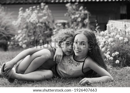 Two Happy little girls laughing and hugging at the summer park. Happy Kids concept.  Black and white photo Foto stock ©
