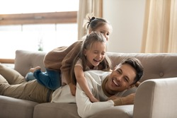 Two happy little girls playing lying on couch with father, smiling young dad having fun with preschool daughters, laughing, relaxing on cozy sofa at home, funny family activity, enjoying weekend