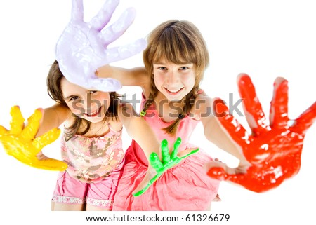 Two happy little girls showing their painted colorful  hands to the camera