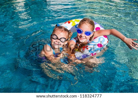two happy little girls splashing around in the pool