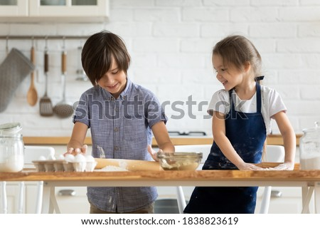 Two happy little kids siblings cooking together, rolling out dough, standing at wooden countertop in modern kitchen, cute preschool sister and brother preparing homemade pastry or pie for parents