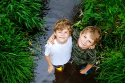 Two happy little school kids boys, funny siblings having fun together walking through water in river in gum rubber boots. Family portrait of healthy brothers and best friends