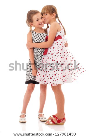 Two happy little sisters kissing isolated on white
