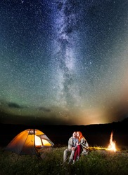 Two happy lovers covered with a plaid sitting together near campfire and camp at night under stars and looking to the starry sky and Milky way