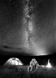 Two happy lovers covered with a plaid sitting together near campfire and camp at night under stars and looking to the starry sky and Milky way. Black and white