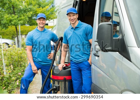 Two Happy Male Cleaners Standing With Vacuum Cleaner Near The Van