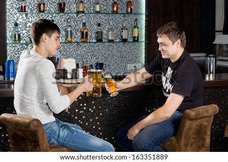 Two happy male teenagers sitting at the bar holding glasses of beer, toasting, with shelves with bottles of alcoholic beverages iin the background