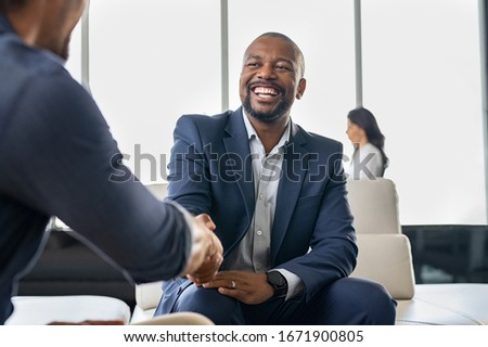 Two happy mature business men shaking hands in office. Successful african american businessman in formal clothing closing deal with handshake. Multiethnic businessmen shaking hands during a meeting.