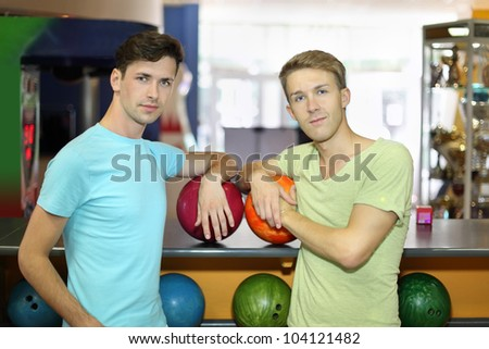 Two happy men with balls stand near counter and look at camera in bowling club; shallow depth of field