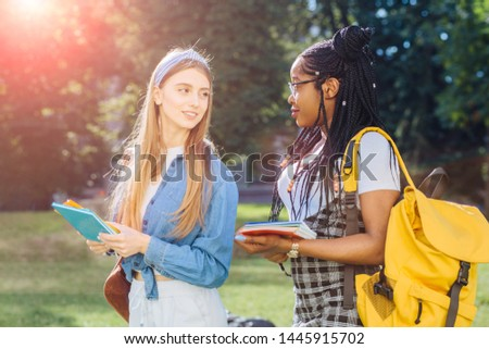 Two happy multiethnic girls as friends with backpaks talking with each other in cheerful way. Cheerful females in university campus park outdoor. Youth Friendship Together Smiling Happiness Concept. #1445915702