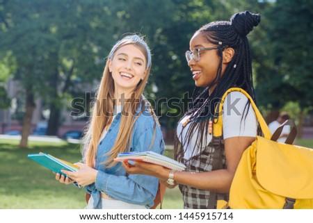 Two happy multiethnic girls as friends with backpaks talking with each other in cheerful way. Cheerful females in university campus park outdoor. Youth Friendship Together Smiling Happiness Concept. #1445915714