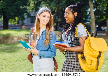 Two happy multiethnic girls as friends with backpaks talking with each other in cheerful way. Cheerful females in university campus park outdoor. Youth Friendship Together Smiling Happiness Concept. #1445915717