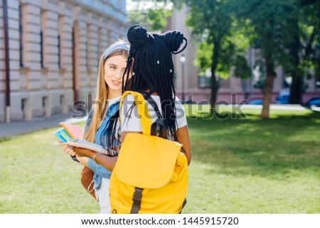 Two happy multiethnic girls as friends with backpaks talking with each other in cheerful way. Cheerful females in university campus park outdoor. Youth Friendship Together Smiling Happiness Concept. #1445915720
