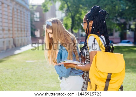 Two happy multiethnic girls as friends with backpaks talking with each other in cheerful way. Cheerful females in university campus park outdoor. Youth Friendship Together Smiling Happiness Concept. #1445915723