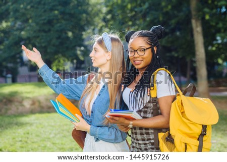 Two happy multiethnic girls as friends with backpaks talking with each other in cheerful way. Cheerful females in university campus park outdoor. Youth Friendship Together Smiling Happiness Concept. #1445915726