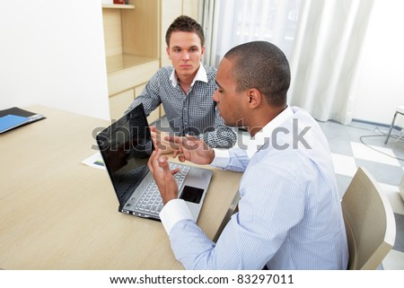 Two happy multinational business man sitting at the table