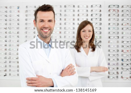Two happy opticians optometrists standing in optician store.
