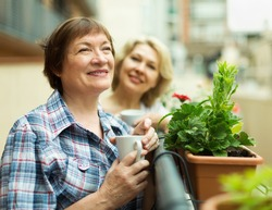 Two  happy pensioner drinking coffee on balcony and smiling