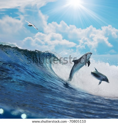 Two happy playful dolphins leaping from ocean breaking surfing wave to foam in front of cloudy seascape