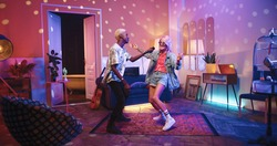 Two happy positive multi-ethnic youth dancing moving rhythmically in good mood at home party, male and female friends having fun energetically moving in room in neon disco light, retro style concept