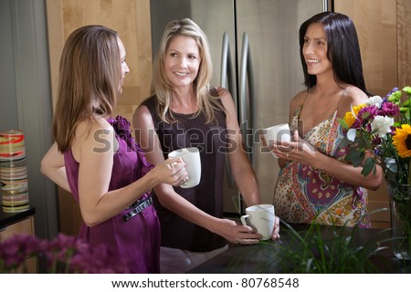 Two happy pregnant women with friend in a kitchen