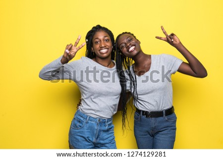 Two happy pretty pretty african women posing together and showing peace gestures while over yellow background