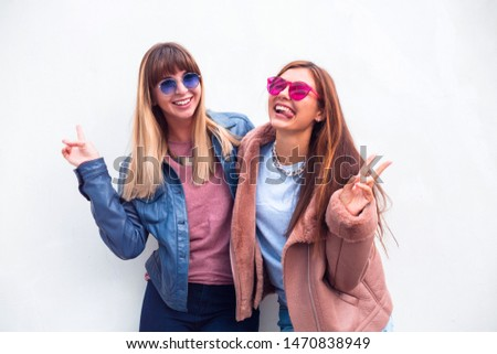 Two happy pretty pretty women in blue and pink leather jackets posing together and showing peace gestures while looking at the camera over white background outdoor.Picture of two playful girls