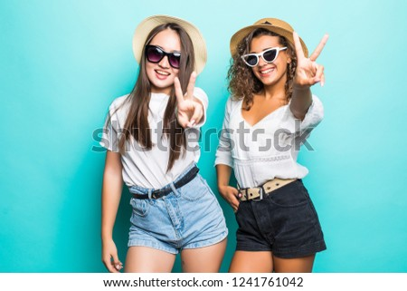 Two happy pretty pretty women in pajamas posing together and showing peace gestures over green background
