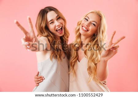 Two happy pretty pretty women in pajamas posing together and showing peace gestures while looking at the camera over pink background