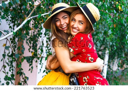 Two happy pretty young sisters, hugs smiling laughing  and having funny crazy time together, bearing stylish retro vintage feminine clothes and hats. Outdoors.