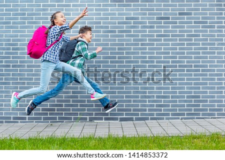 Two happy schoolchildren with backpacks run to school on street next to an Brick Wall. Cheerful cute children pupils Teen Girl and Boy Back to School. Concepts of friends, childhood and education. #1414853372