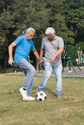 Two happy senior men playing the football at park outdoor