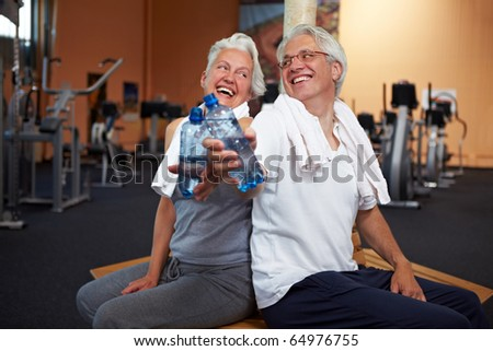 Two happy senior people in a gym drinking water