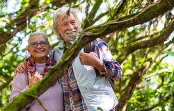 Two happy senior people smiling enjoying mountain hike in the woods among trunks and branches covered with moss during autumn season - concept of fun and active retired seniors