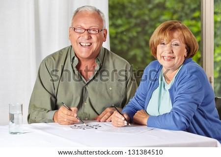 Two happy senior people solving riddles in a retirement home