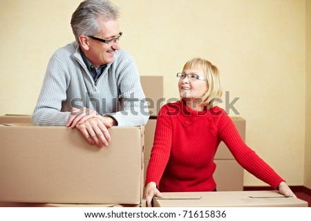 Two happy senior people with many moving boxes