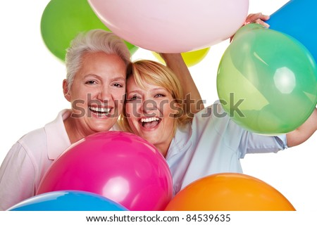 Two happy senior women cheering with many balloons