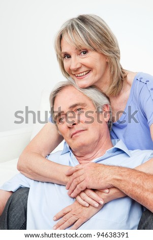 Two happy seniors embracing each other at home on couch