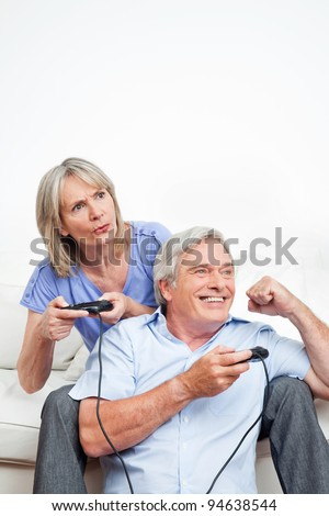 Two happy seniors playing video games at home