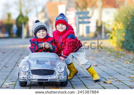 Two happy sibling boys in red jackets and rain boots playing with big old toy car, outdoors.  Kids leisure on cold day in winter, autumn or spring.