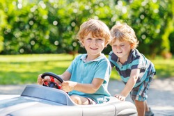 Two happy sibling boys playing with big old toy car in summer garden, outdoors. Selective focus on child in car.