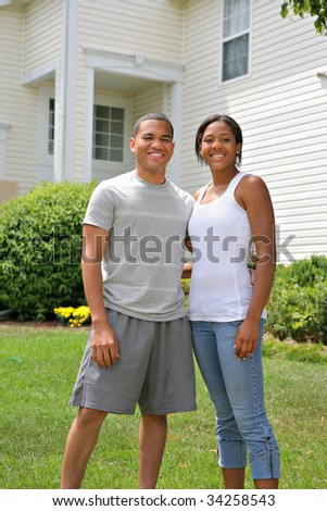 Two Happy smiling African American Home Owners in front of House