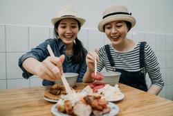 two happy smiling asian girls travelers love delicious food trying taiwanese local meal sitting in vendor traditional restaurant shop store. young women cheerful using chopsticks ready to eat.