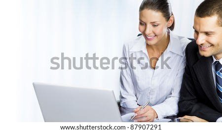 Two happy smiling cheerful business people working with laptop at office, with copyspace area