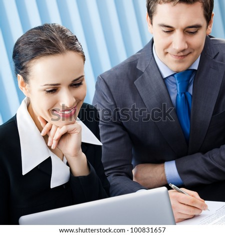 Two happy smiling cheerful young businesspeople working with laptop at office