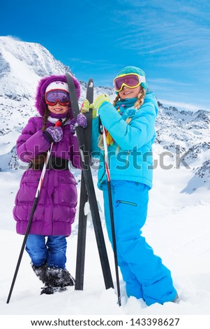 Two happy smiling girls with cross country ski standing together at winter