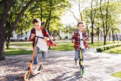 Two happy smiling teenagers brothers, 7 and 8 years old, with speed riding a scooter in the park on a summer evening. Dressed in plaid checkered red shirt, white and jeans. Happy urban childhood.