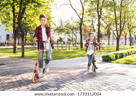 Two happy smiling teenagers brothers, 7 and 8 years old, with speed riding a scooter in the park on a summer evening. Dressed in plaid checkered red shirt, white and jeans. Happy urban childhood. Stock photo ©